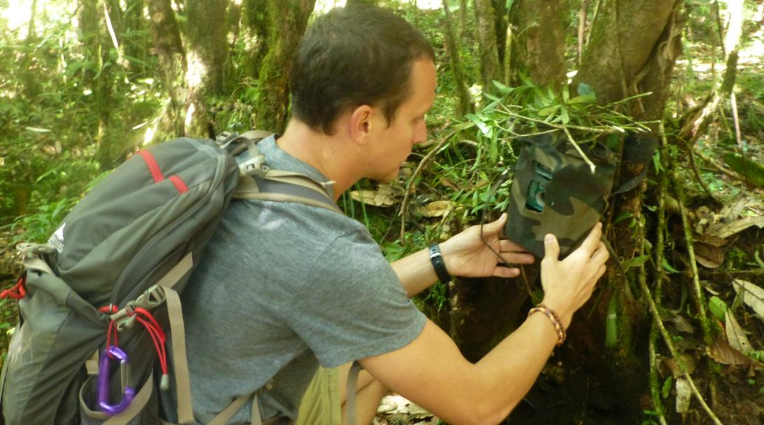 Mountain conservation volunteer in Nepal setting up a camera trap.